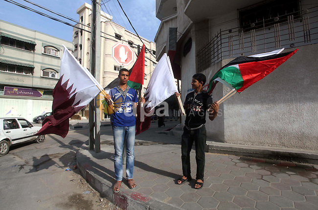 Palestinians carry the Qatari and Palestinian (red,black,white, green) flags in Gaza City on October 21, 2012, the day before the Emir of Qatar's official visit to the strip. Emir of Qatar Hamad bin Khalifa Al Thani visit Gaza to oversee and sponsor the implementation of several rehabilitation projects, including repair of the vast damage still remaining from Israel's December 2008 Operation Cast Lead. Photo by Ashraf Amra