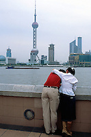 "China. Shanghai. Downtown. City center. Pudong skyline seen from ""The Bund"". A couple shares tender and passionate moments near the river. Over 1 and 1/2 times larger than urban Shanghai itself, the Pudong new area consists of the entire eastern bank of the Huangpu river. Pudong is the new area of development where the growing business needs constantly new modern high buildings, real ""skyscrapers"". Pudong has become Shanghai and China's economic powerhouse.The highest tower is the Oriental Pearl Tower wits 11 pink baubles.The Bund is the most impressive 2 km in Shanghai.  © 2002 Didier Ruef"