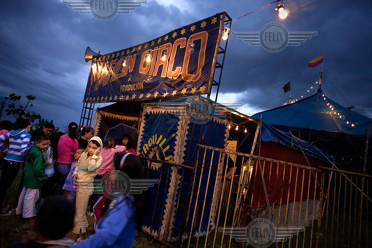 People wait outside the Marlin Circus at dusk before an evening performance. Around a dozen small circuses wander the poorer neighbourhoods around the city of Medellin putting on performances in what can be a hand to mouth existence. Despite falling audience numbers, new health and safety regulations and other bureaucracy these small family businesses, many of whom have existed for generations, still scrape a living in a world where the people are more accustomed to being entertained by soap operas than by live entertainment.