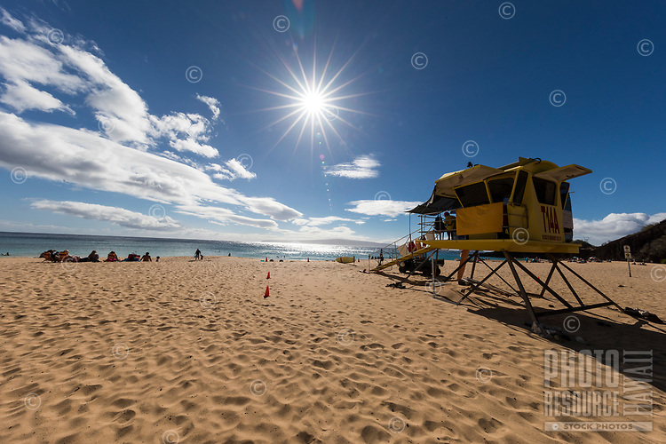 Beachgoers near a lifeguard tower enjoy a clear day at Makena Beach, Maui.