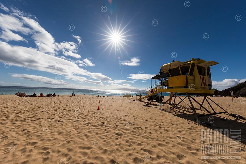 Beachgoers near a lifeguard tower enjoy a clear day at Makena Beach, Maui.