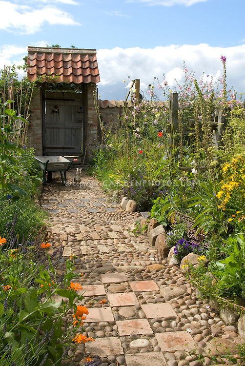 Garden path of stones, pebbles & tiles leading to garden gate door, with wheelbarrow, chicken, vegetable and flower garden borders, blue sky and clouds, wide view