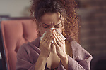 Woman blowing her runny nose or sneezing in a paper tissue