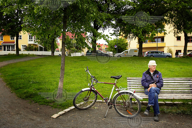 An elderly man sits on a bench outside a sports arena.