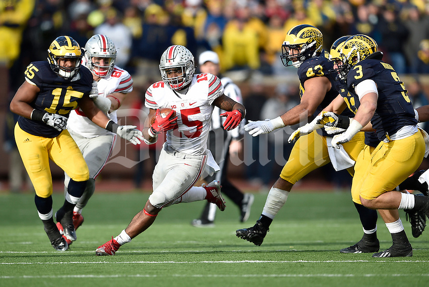 Ohio State Buckeyes running back Ezekiel Elliott (15) finds a hole in the Michigan Wolverines defense in the fourth quarter of the college football game between the Michigan Wolverines and the Ohio State Buckeyes at Michigan Stadium in Ann Arbor, Saturday afternoon, November 28, 2015. The Ohio State Buckeyes defeated the Michigan Wolverines 42 - 13. (The Columbus Dispatch / Eamon Queeney)