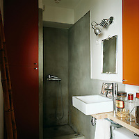 A simple bathroom has a shower in an open recess and a washbasin set on a shelf