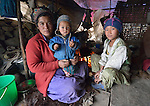 Ugre Tamang and her daughters Mingmar, 10, and Suchita, 11 months, sit by the fire in their family's temporary shelter in the village of Gatlang, in the Rasuwa District of Nepal near the country's border with Tibet.<br /> <br /> In the aftermath of the April 2015 earthquake that ravaged Nepal, the ACT Alliance helped people in this village with a variety of services, including blankets, shelter and livelihood assistance.