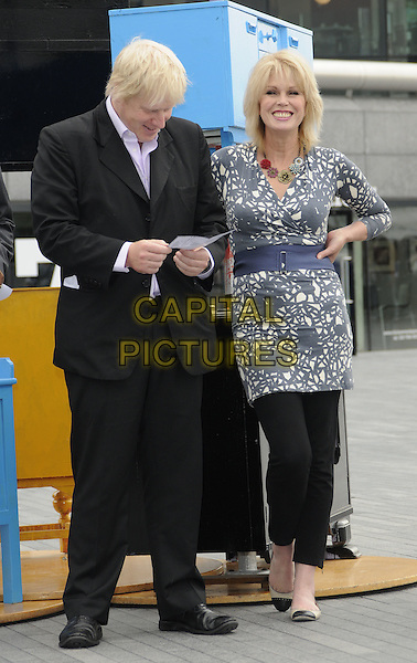 BORIS JOHNSON (Mayor of London) & JOANNA LUMLEY.The launch of the old furniture recycling scheme, The Scoop, More London, the Queen's Walk, London, England..July 12th, 2010.full length black suit grey gray white print top blue waist belt trousers leggings looking down hand on hip .CAP/CAN.©Can Nguyen/Capital Pictures.