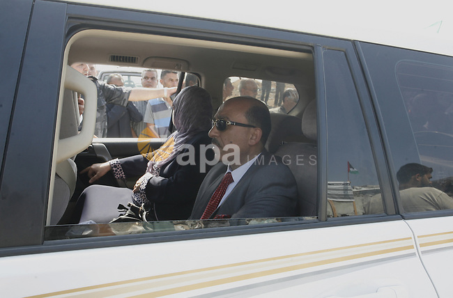 Palestinian minister of housing Mufid al-Hasayna rides his car during the visit of Prime Minister Rami Hamdallah to the Beit Hanoun in the northern Gaza Strip on October 9, 2014. The Palestinian unity government which took the oath of office in June under technocrat prime minister Rami Hamdallah arrived to Gaza Strip on Thursday to convene the first fully meeting. Hamdallah said that the unity government will rebuild the bombed-out Gaza Strip following a seven-week Israeli offensive. Photo by Abed Rahim Khatib