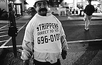 This migrant worker hands out flyers for call-girls and displays a shirt in which advertising strippers. The Las Vegas strip is lined with migrant workers at night doing this same kind of work. Las Vegas, Nevada, USA,  November 2003 © Stephen Blake Farrington