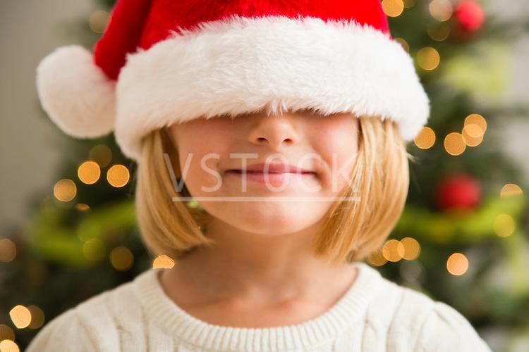 Girl (6-7) wearing Santa hat