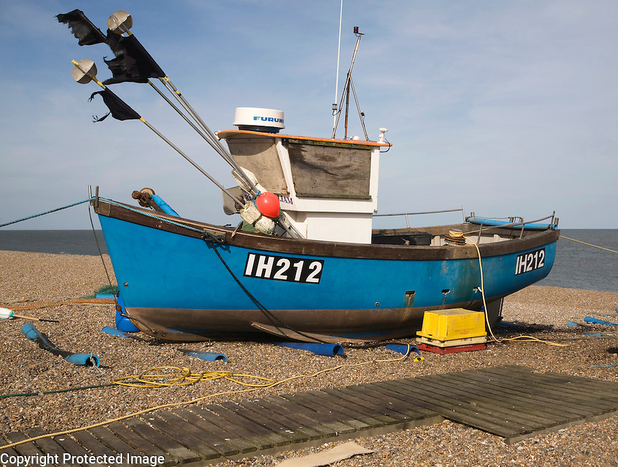 Fishing boats and equipment on the shingle beach at Aldeburgh, Suffolk, England