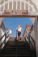 Writer Conor Mihell with a Canadian flag pretends to invade historic Fort Mackinac the site of a War of 1812 battle on Mackinac Island Michigan.