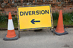 Yellow rectangular diversion sign with arrow pointing standing by two traffic cones, UK