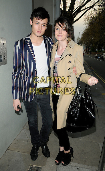 "DOUGLAS BOOTH (Burberry model) & GUEST .The ""Cherrybomb"" VIP screening, Beaufort House, London, England..April 20th, 2010.full length jeans denim blue red white striped stripes blazer jacket beige mac trenccoat black bag purse open to ankle boots leggings .CAP/CAN.©Can Nguyen/Capital Pictures."