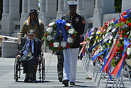 Washington, DC - June 6, 2014: WWII veteran Henry Mendoza (seated) is escorted by John McCaskill, of the Nation Park Service, during a wreath laying ceremony at the National World War II Memorial. The ceremony was part the 70th anniversary of the D-Day invasion honoring WWII veterans. Mendoza was a member of the 9th Air Force in the months leading up to Operation Overlord. (Photo by Don Baxter/Media Images International)