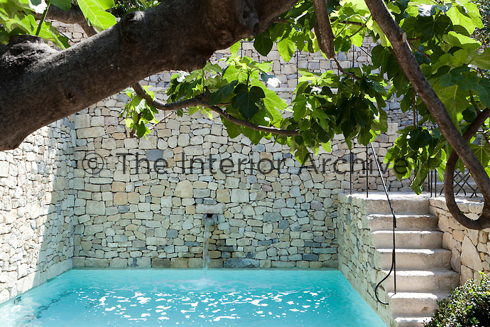The cool waters of this outdoor pool are enclosed by a series of stone terraces