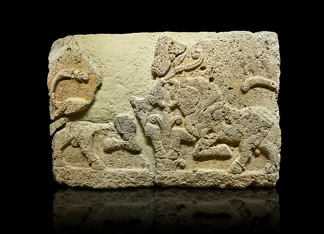 Photo of Hittite relief sculpted orthostat stone panel of Herald's Wall Limestone, Karkamıs, (Kargamıs), Carchemish (Karkemish), 900-700 B.C. Anatolian Civilisations Museum, Ankara, Turkey.<br /> <br /> A pair of kneeling bull on either side of the tree of life, one each foot is on the tree, the other feet are bend towards the abdomen.  <br /> <br /> Against a black background.