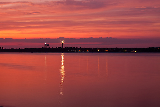 The Pensacola Light reflecting on water as seen  from Fort Pickens at night Sunset