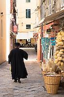 Greek Orthodox priest in traditional robes in street scene in Kerkyra, Corfu Town, Greece