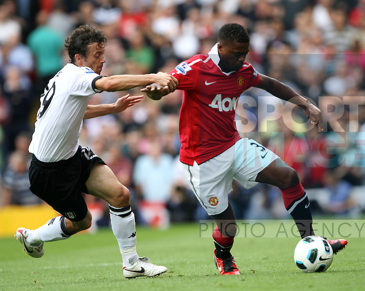 Fulham's Simon Davies tussles with Manchester United's Patrice Evra