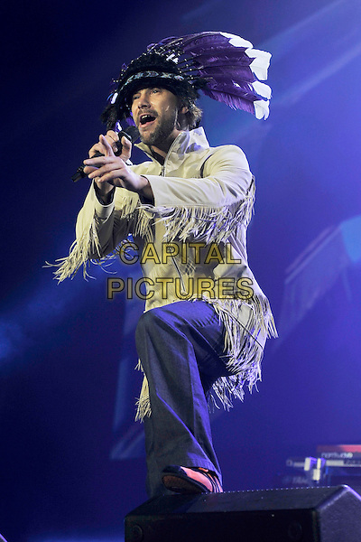 JAY KAY of JAMIROQUAI.Jamiroquai live at the O2 Arena, London, England, UK, April 15th 2011..music concert gig on stage half full  length microphone singing  indian feather headdress hat tassels fringed jacket costume yellow jason foot .CAP/MAR.© Martin Harris/Capital Pictures.