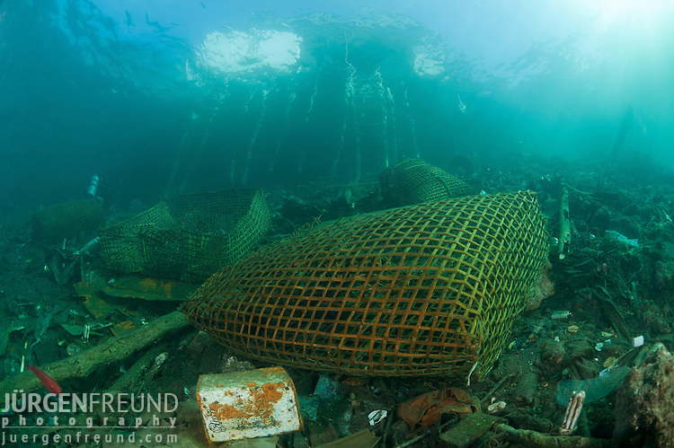 Fish trap in amongst human trash and waste thrown out to the coastal waters settling on the ground becoming marine life habitat.