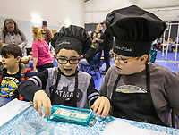 Judah Libertini (left), 10, and Jonah Wright, 12, of Springdale count their income Tuesday, Feb. 11, 2020, at their business Cookie O'Clock during the Social Homeschoolers Network annual Junior Entrepreneur Fair at Rogers Christian Church. Pre-kindergarten through high school students in the group created businesses and sold their home-made products and services to the public during the fair. Judges also awarded prizes to the best businesses by age group. Check out nwaonline.com/200212Daily/ for today's photo gallery.<br /> (NWA Democrat-Gazette/Ben Goff)
