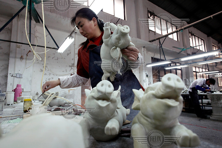 A worker paints a novelty garden pig figurine, made from petroleum resin (C9), at the Chuan Sen Art & Design Factory on the outskirts of Guangzhou.