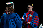 Students receive their degrees from the Rev. Dennis H. Holtschneider, C.M., president of DePaul, Saturday, June 10, 2017, during the DePaul University College of Education commencement ceremony at the Rosemont Theatre in Rosemont, IL. (DePaul University/Jeff Carrion)