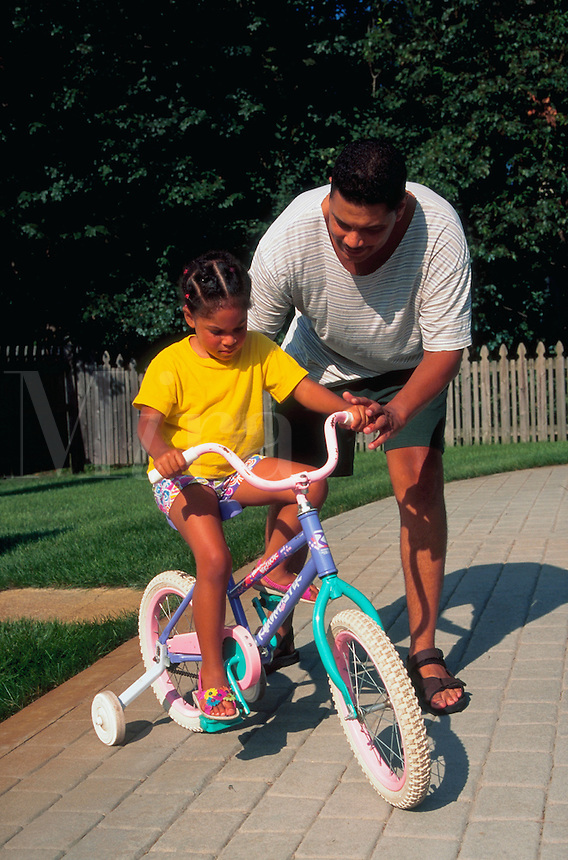African American father teaching his daughter how to ride her bicycle; bike has training wheels.
