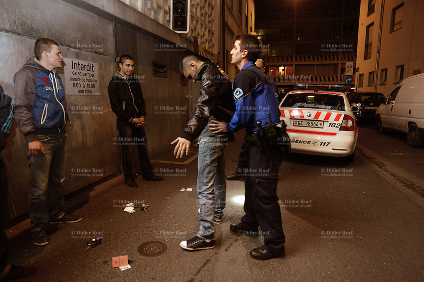 Switzerland. Geneva. A police officer is frisk searching a man in a narrow street at night. A frisk search (also called a patdown or pat down) is a search of a person's outer clothing wherein a person runs his or her hands along the outer garments to detect any concealed weapons or contraband. Both police officers control the identities of a group of young men and look for illegal substances (drugs). The men come from the neighboring french area and want to party in the Paquis neighborhood, known for its nightlife and Red-light district. They will all be left free after the control. The policeman is wearing a ballistic vest, bulletproof vest or bullet-resistant vest which is an item of personal armor that helps absorb the impact from knives, firearm-fired projectiles and shrapnel from explosions, and is worn on the torso. Soft vests are made from many layers of woven or laminated fibers and can be capable of protecting the wearer from small-caliber handgun and shotgun projectiles. 01.04.12 © 2012 Didier Ruef..