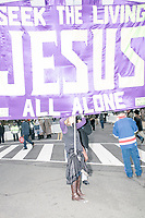 "A woman holds a large religious banner that reads ""Seek the living / Jesus / All Alone"" as people leave the National Mall after the inauguration of President Donald Trump on Jan. 20, 2017, in Washington, D.C."