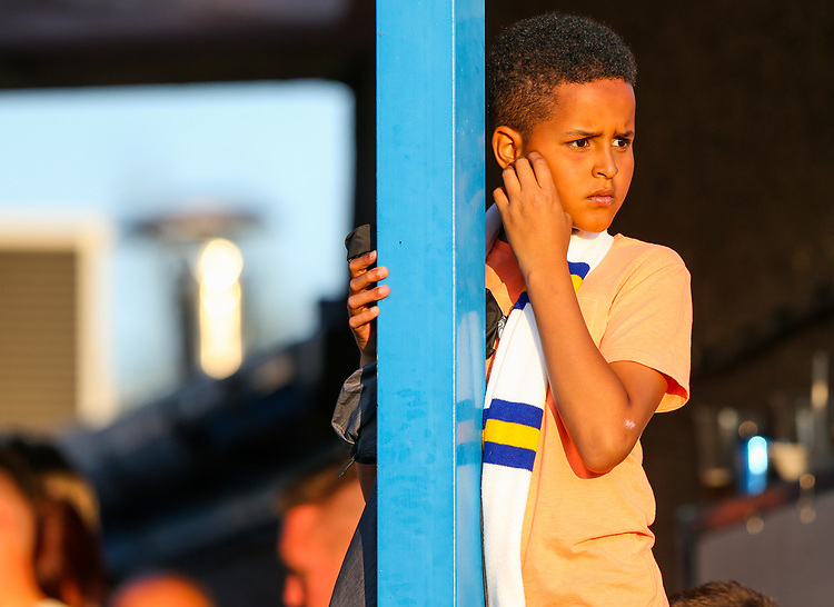 A young Leeds United fan watches on<br /> <br /> Photographer Alex Dodd/CameraSport<br /> <br /> Football Pre-Season Friendly - Guiseley v Leeds United - Thursday July 11th 2019 - Nethermoor Park - Guiseley<br /> <br /> World Copyright © 2019 CameraSport. All rights reserved. 43 Linden Ave. Countesthorpe. Leicester. England. LE8 5PG - Tel: +44 (0) 116 277 4147 - admin@camerasport.com - www.camerasport.com