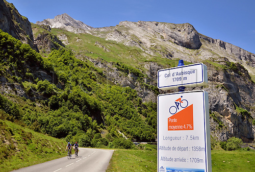 05.06.2012. Pyrenees Mountains, France.  Two cyclists pass a sign with information relatiing to  length and altitude of the pass route, at the eastern climb to Col d'Aubisque (1709m) in the French Pyrenees. The pass is part of the Tour de France