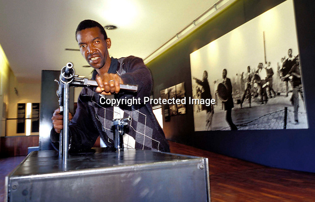 digasow00071.South African Places. Gauteng. Soweto. An unidentified man looking at homemade guns in the newly opened Hector Peterson museum on June 14, 2002 in Soweto, South Africa. Hector Peterson was killed during the student uprising in Soweto in 1976, where black students demonstrated against the Afrikaans language imposed by them by the Apartheid government. The new museum opened on Youth Day June 17, 2002..©Per-Anders Pettersson/ iAfrika Photos