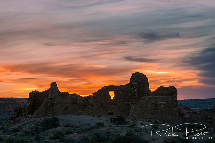 The sun sets behind Pueblo Del Arroyo. The site of Pueblo Del Arroyo lies within the Chaco Culture National Historic Park in New Mexico.