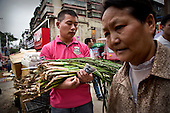 A farmer sells crops in southwestern China next to tall buildings in an area that was entirely rural only a few years ago.  <br /> <br /> China is pushing ahead with a dramatic, history-making plan to move 100 million rural residents into towns and cities over the next six years.<br /> <br /> Moving farmers to urban areas is touted as a way of changing China&rsquo;s economic structure, with growth based on domestic demand for products instead of exporting them.