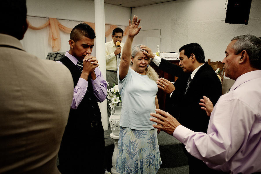 Central Falls, Rhode Island, July 15, 2012 - Pastor Narciso Romero (second from right) prays over one of his congragants at Iglesia Pentecostal Unida. Churches and religious organizations are helping to fill some gaps and keeping the community together. Iglesia Pentecostal Unida hosts events several nights each week for its congregation. <br />