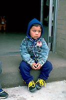 Pensive four year old boy sitting at Cinco de Mayo celebration.  St Paul Minnesota USA