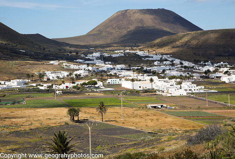 View over cactus plants and whitewashed houses to Monte Corona volcano cone, village of Maguez, Lanzarote, Canary Islands, Spain