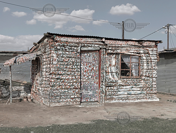 A neat wooden shack that has been painted in a multi-coloured dappled style. Graeme Williams' pictures of the environments occupied by some of South Africa's poorest people focus on the interiors and exteriors of people's homes, accentuating the minutiae of the occupants' day-to-day dwelling places. The bright colours captured in these photographs are suggestive of resilience, hope and a sense of humanity that survives in these poverty-stricken communities...