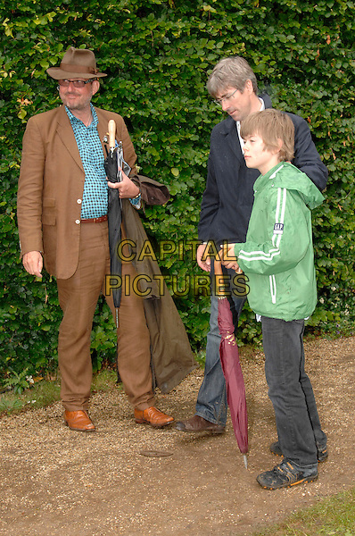 PETER DE SAVORY & TIM TAYLOR with son.at Goodwood Festival Of Speed, Goodwood, West Sussex, England, June 24th 2007..full length brown suit hat glasses green jacket top child umbrella.CAP/FIN.©Steve Finn/Capital Pictures.