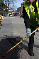 David Dollosa fills potholes with asphalt while working for the Boston Public Works Department in Boston, Massachusetts, USA, on April 12, 2012. The city uses a computer system to track public complaints and record work done by city crews to mitigate these complaints.  A supervisor or inspector photographs before and after pictures of the work in addition to making notes about the work done.
