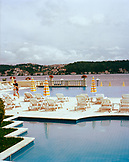 TURKEY, Istanbul, chairs arranged by swimming pool at the Kempinski Hotel with the Bosporus in the background
