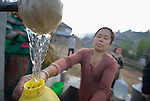 A woman fills a container with water at a community spigot in Makaising, a village in the Gorkha District of Nepal that suffered badly in a devastating 2015 earthquake.
