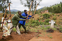 Rwanda. Western province. Nyange. Genocide Memorial. A group of Tutsis take care of all that remains of the Nyange church which are piles of weed-strewn rubble, with four concrete crosses marking mass graves. In 1994, Father Seromba, a hutu extremist, gave the order to bulldoze his own church on top of his own congregation of 3'000 tutsi people.   © 2007 Didier Ruef