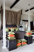 A four poster bed with a check pattern canopy and cushions in green and orange in a bedroom of Lower Slaughter Manor, now a hotel in Gloucestershire