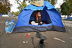 A woman from Afghanistan looks out from her tent in a city park in Belgrade, Serbia. The park has filled with refugees from Syria and other countries on their way to western Europe.