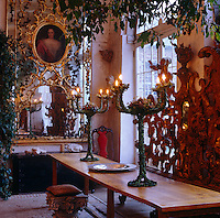 A gilded rococo overmantel incorporating a portrait hangs at one end of this dining room furnished with a narrow contemporary table
